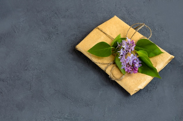 Lente samenstelling. mooie geschenkdoos omwikkeld met bruin kraftpapier en versierd met een bos lila op een donkere achtergrond. bovenaanzicht, kopieer ruimte voor tekst.