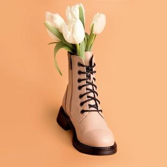 Lente schoenen. laars met witte tulpen op een beige achtergrond