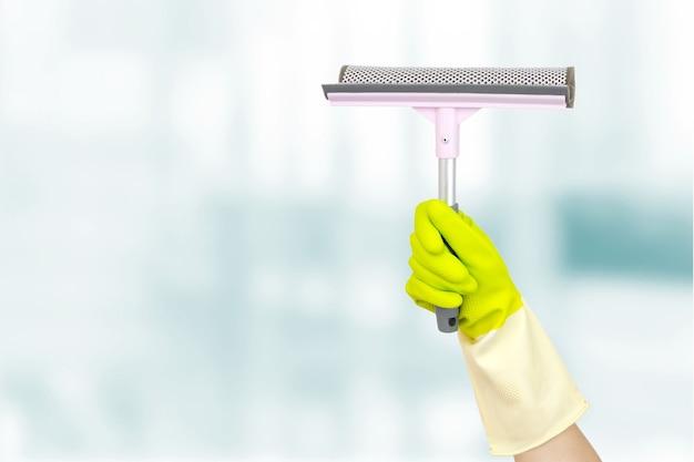 Lente schoonmaak concept. hand die een roze schrapervensters op een blauwe achtergrond houdt. hand met gereedschap voor het reinigen van ramen. schoonmaak leveringen concept.