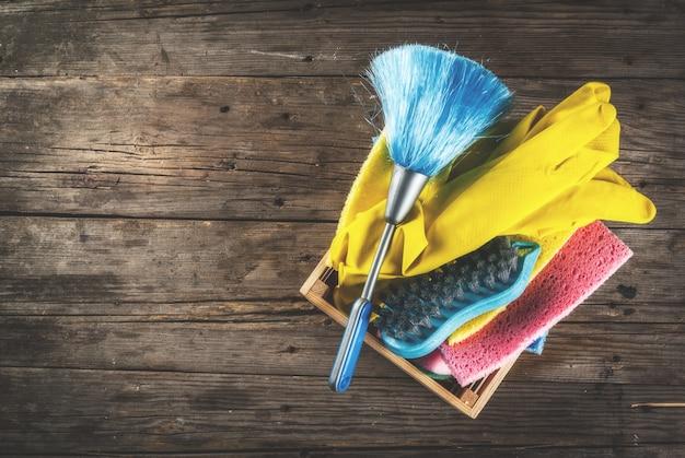 Lente schoonmaak concept met leveringen, huis schoonmaak producten stapel. het concept van het huishoudenkarwei, op plattelander of tuin houten achtergrondexemplaar ruimte hoogste mening