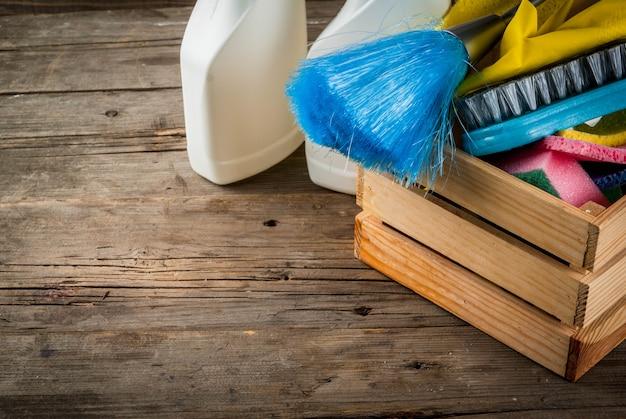 Lente schoonmaak concept met leveringen, huis schoonmaak producten stapel. het concept van het huishoudenkarwei, op plattelander of tuin houten achtergrondexemplaarruimte