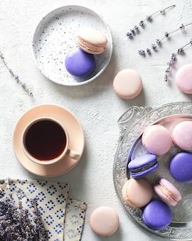 Lente stemming met kleur bitterkoekjes kopje koffie en bloemen over witte textuur, bovenaanzicht