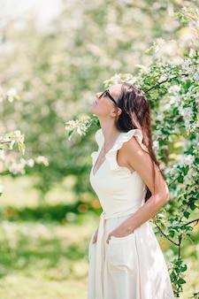 Lente stemming mooie vrouw geur bloeiende boom genieten van natuur witte bloementuin