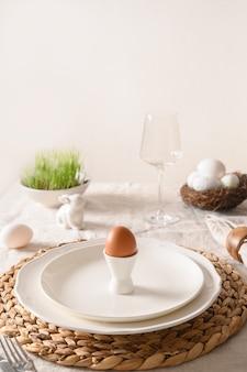 Lente stilish paastafel setting met biologische eieren, konijn en bloeiende bloemen.