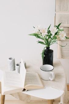 Lente stilleven. ontbijt op bed. witte slaapkamer. lief huis. boeken, bloemen en koffiekopje. plat leggen