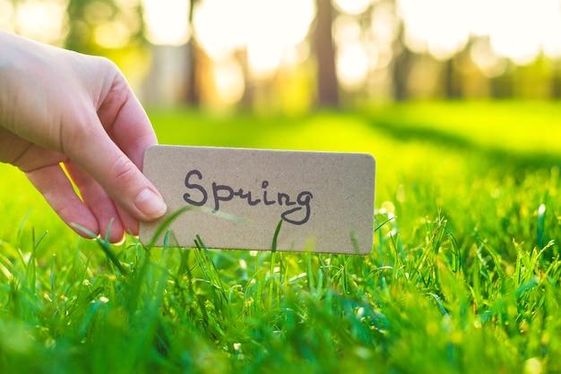 Lente tekst op een kaart. de holdingskaart van het meisje in stralen in het lentepark.