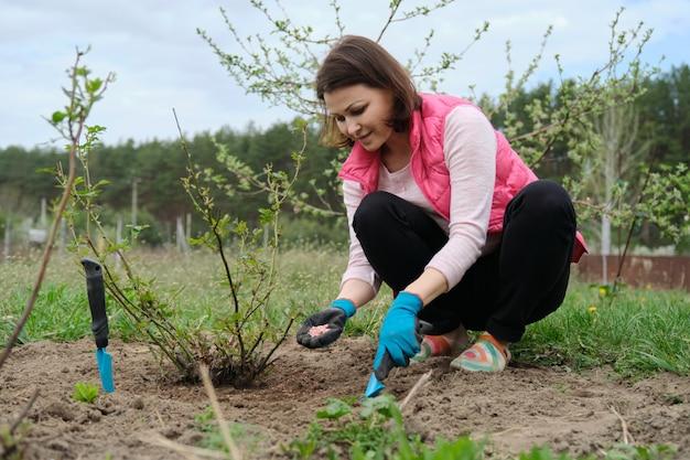 Lente tuinieren, vrouwelijke tuinman die in handschoenen met tuingereedschap werkt