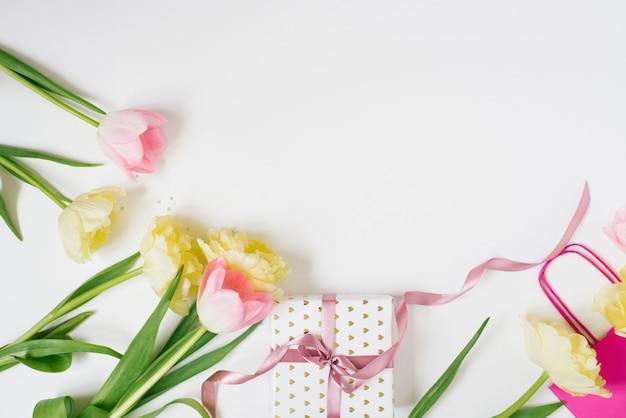 Lente tulp bloemen en geschenkdoos op lichttafel bovenaanzicht in platte lay-stijl. wenskaart voor verjaardag, valentijn vrouw of moederdag