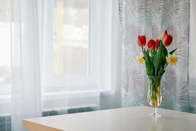 Lente tulpen in een glazen vaas op tafel
