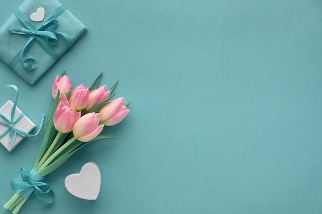 Lente turkoois papier met roze tulpen en ingepakte geschenken, kopie-