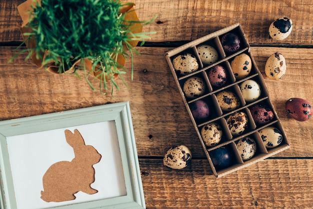 Lente vakantie. bovenaanzicht van paashaas in fotolijstje en doos met paaskwarteleitjes liggend op houten rustieke tafel