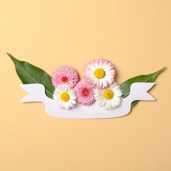Lente vakantie concept. creatieve lay-out gemaakt van papier lint met groene bladeren en madeliefjebloemen