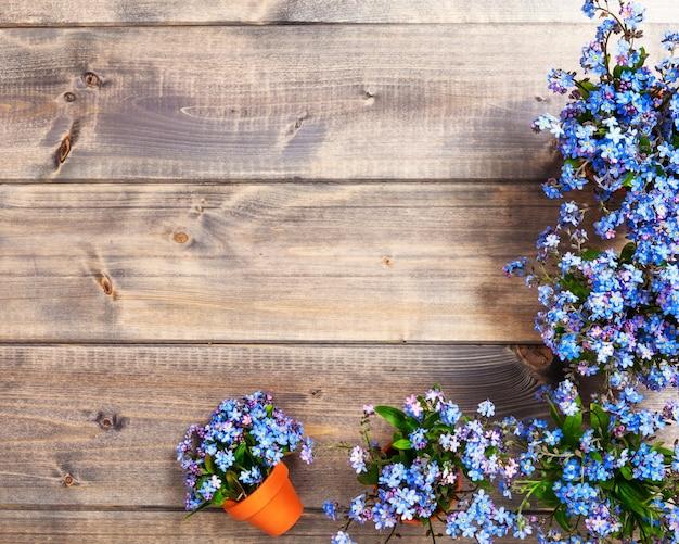 Lente vergeet me niet bloemen op houten achtergrond, bovenaanzicht, plat lag