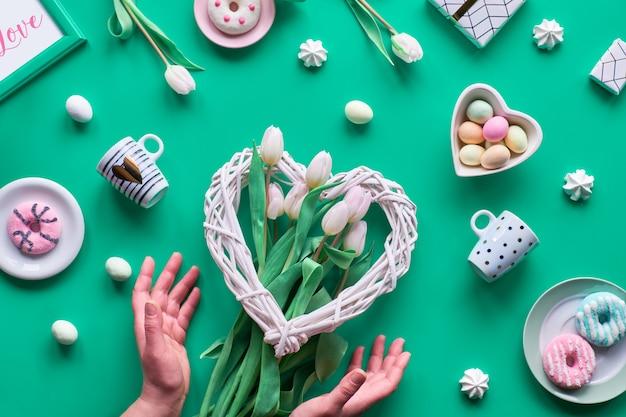 Lente verjaardag of jubileum. wattled hart, paaseieren in hart kom, koffiekopjes, verse tulpen, geschenken. geometrische lente plat lag in wit en roze op groene muur pasen, moederdag,