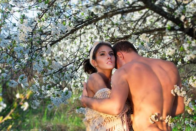 Lente verliefde paar. zomers geluk. sensuele minnaars in kersenbloesemboom.