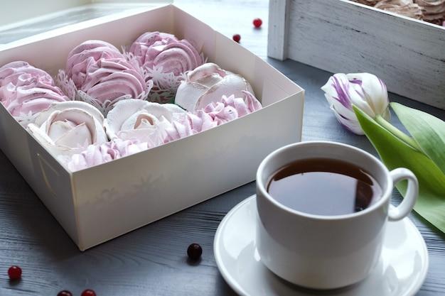 Lente viering plat leggen. witte kop met koffie, roze tulpen en marshmallows. vakantie achtergrond. wenskaart.