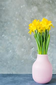 Lente wenskaart. lentebloemen, gele narcissen in een vaas op een grijze achtergrond