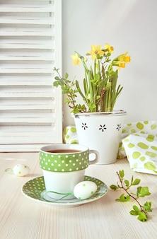Lente wenskaart ontwerp met gele narcissen en kopje koffie op licht hout