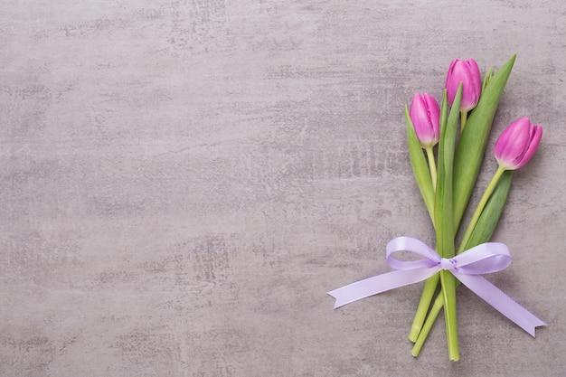 Lente wenskaart, roze kleur tulpen op het grijs.
