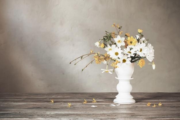 Lente witte en gele bloemen op de oude muur als achtergrond