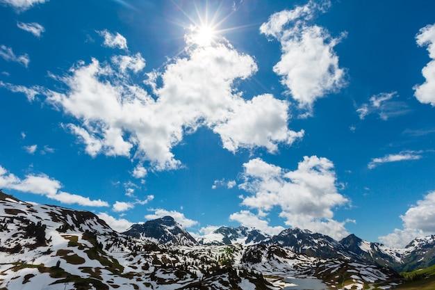 Lente zonnige alpen bergzicht vanaf hochtannbergpass met zon en wolken in blauwe lucht (warth, vorarlberg, oostenrijk)