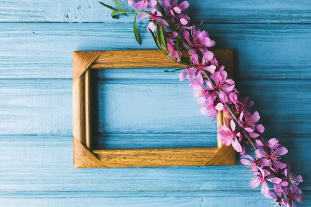 Lentebloemen en frame op een blauwe houten achtergrond