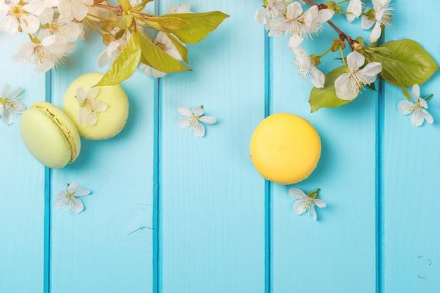 Lentebloemen en kleurrijke bitterkoekjes op de blauwe achtergrond.
