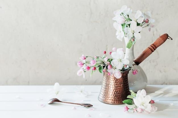Lentebloemen in cezve op witte tafel