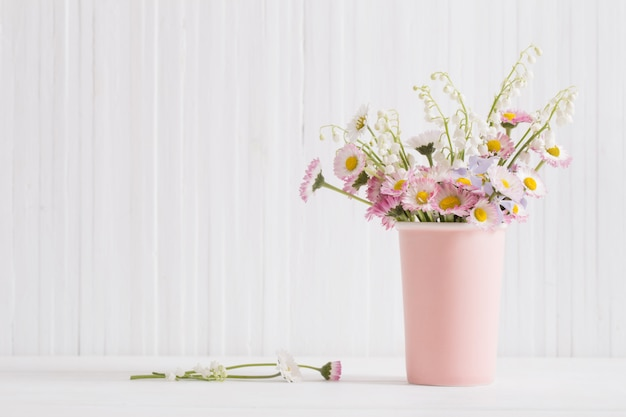 Lentebloemen in vaas op witte houten achtergrond