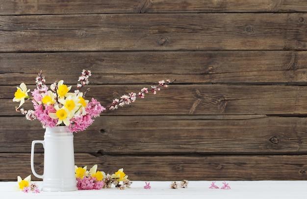 Lentebloemen in witte kruik op houten achtergrond