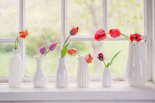 Lentebloemen in witte vaas op oud venster