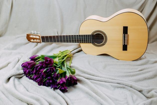 Lentebloemen, paarse tulpen, witte gitaar en bloemen op grijze achtergrond, lente muziek poster.