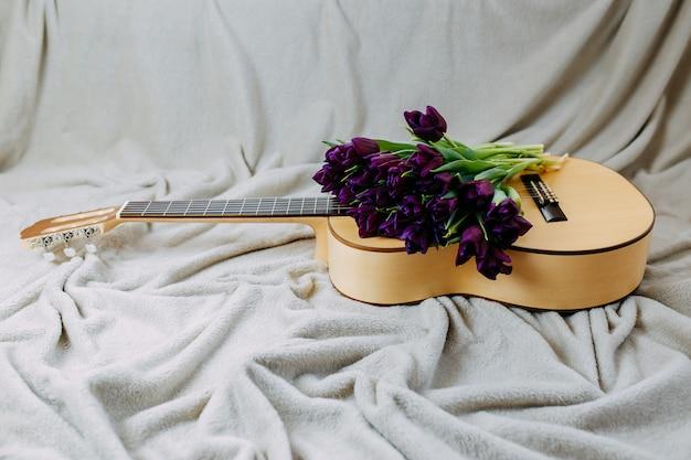 Lentebloemen, paarse tulpen, witte gitaar en bloemen op grijze achtergrond, lentemuziekposter, bos paarse tulpen op de gitaar.