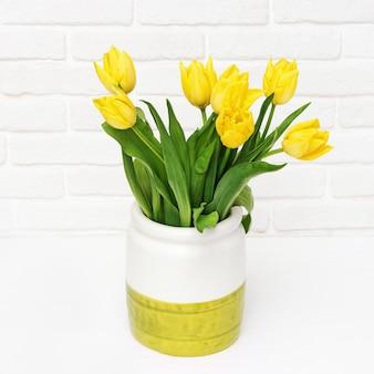 Lentebloemen van tulp in vaas op decoratieve bakstenen muur