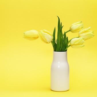 Lentebloemen van tulp in witte keramische vaas op geel