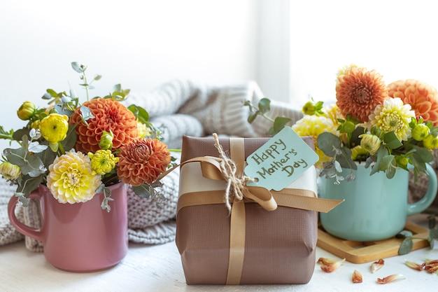 Lentecompositie voor moederdag met een cadeau en chrysantenbloemen
