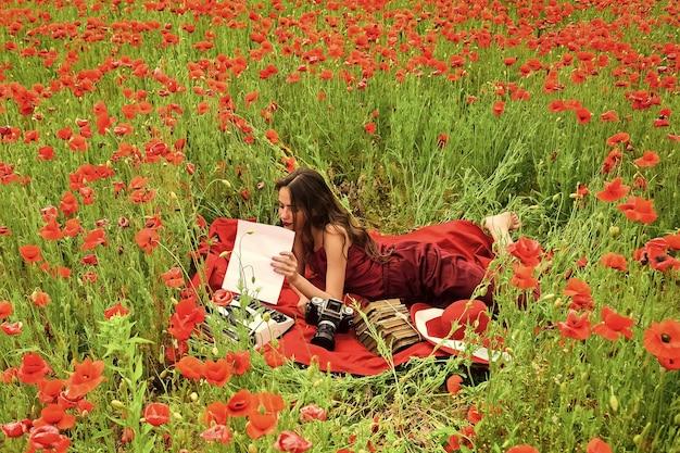 Lentedromen. meisjesjournalistiek en schrijven, zomer. journalistiek fotograaf verslaggever, schrijver vrouw in papaverveld.