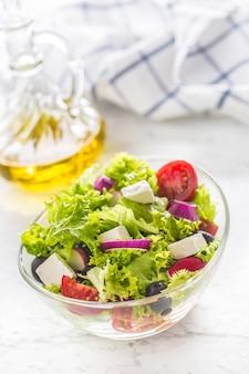 Lentegroentesalade met tomaten-ui-kaas en olijven.