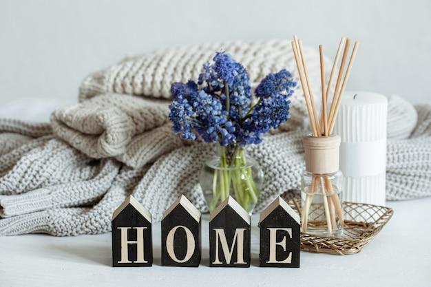 Lentehuissamenstelling met bloemen, aromasticks, gebreid element en decoratief woordhuis.