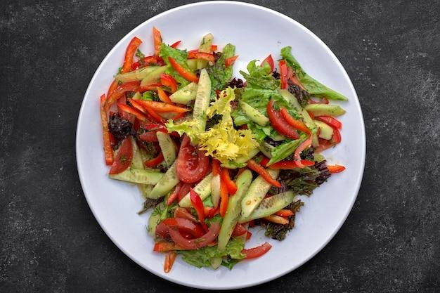 Lentesalade van verse groenten, komkommers, tomaten, sla, paprika op een witte plaat, op een donkere achtergrond