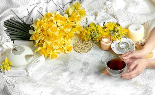 Lentesamenstelling met gele narcissen, decordetails en een kopje thee bij vrouwelijke handen.