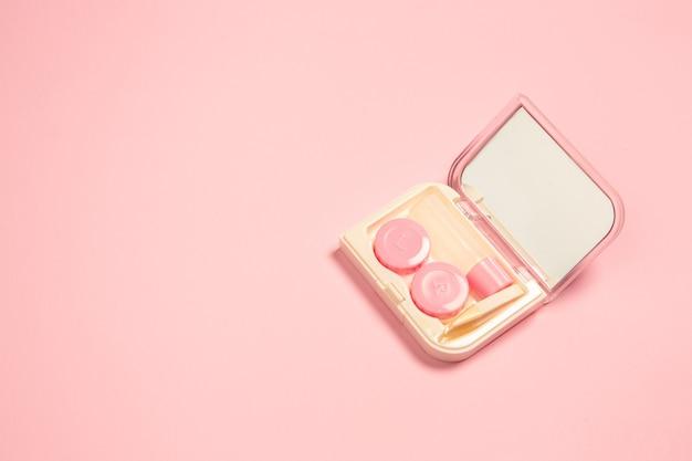 Lenzen in koffer met spiegel. monochroom stijlvolle en trendy compositie in roze kleur achtergrond. bovenaanzicht, plat gelegd. pure schoonheid van de gebruikelijke dingen in de buurt. copyspace voor advertentie. vrouwelijk.