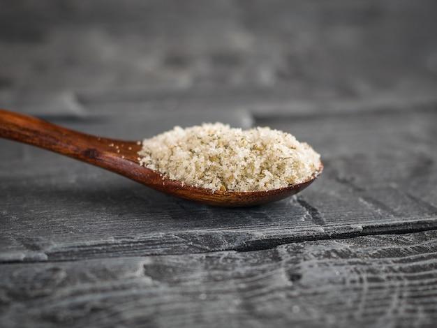 Lepel donker hout tot de rand gevuld met zout met kruiden op een donkere houten tafel