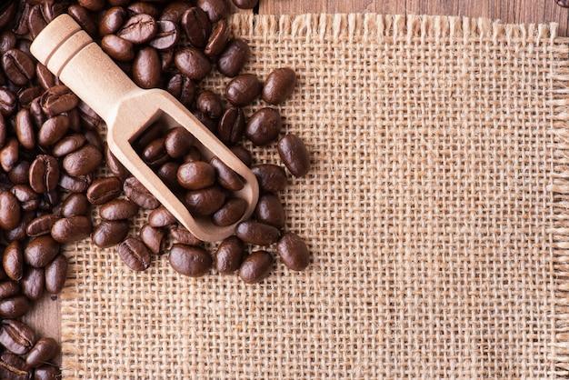 Lepel en koffiebonen op zakachtergrond met exemplaarruimte