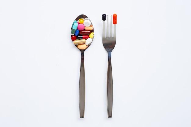 Lepel en mensen met kleurrijke tabletten, capsules en pillen op wit