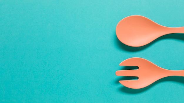 Lepel en vork aan de rand van de blauwe achtergrond