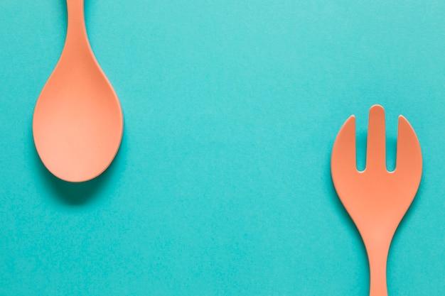 Lepel en vork aan randen van blauwe achtergrond
