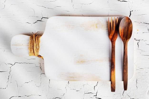Lepel en vork op witte houten snijplank