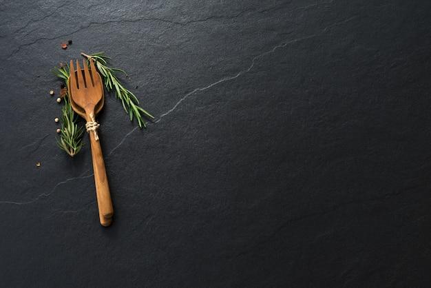 Lepel en vork peper op zwarte marmeren achtergrond met copyspace