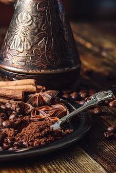 Lepel gemalen koffie en specerijen op metalen plaat.